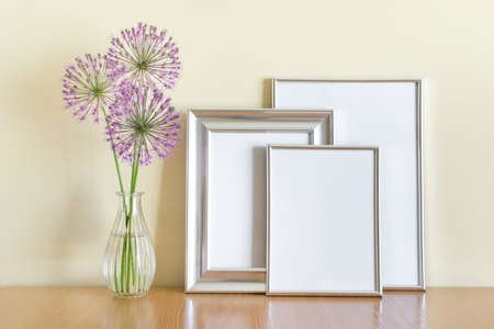 Mockup template with three silver frames and purple flowers in glass vase. 免版税图像