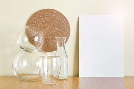 Mockup template composition with glass vases, round cork decor and A4 paper sheet for kitchen recipe or menu or illustration. 免版税图像