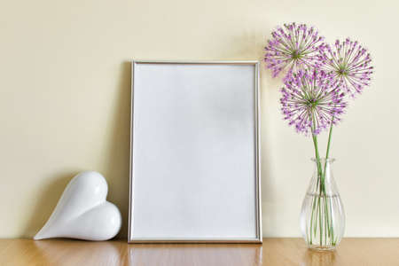 Romantic mockup template with standing A4 silver frame, white porcelain heart and glass vase with purple flowers on wooden shelf.