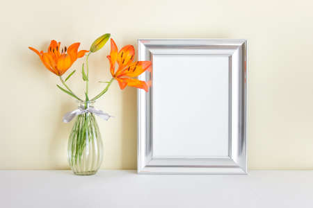 A4 blank wide silver frame with blank empty space surface and orange lily in glass vase standing on white surface.