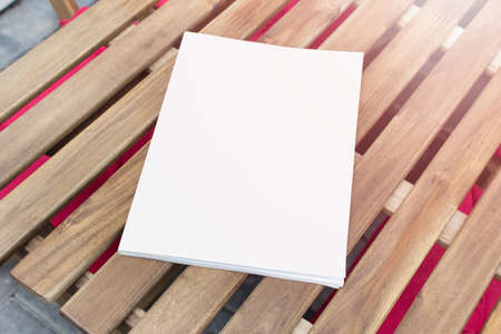 Mockup template of paper book with blank cover laying on wooden table. 免版税图像