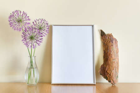 Mockup template with blank silver A4 frame, glass vase, purple flowers and wooden log on wooden surface. 免版税图像