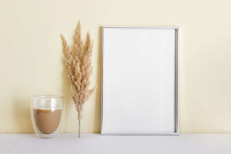 Mockup template with large silver A4 blank frame and coffee with dry yellow plant next to yellow wall.