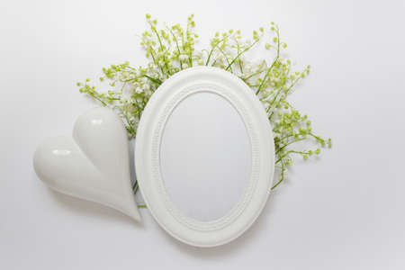 Mockup template with oval white frame with love porcelain heart and forest flowers lilies of valley on white background.