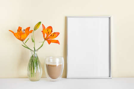 A4 blank silver frame with blank empty space surface, orange lily, morning coffee.