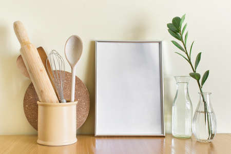 Mockup template with silver metallic blank A4 frame, kitchen wooden utencils, glass vases and green plant branch. 免版税图像