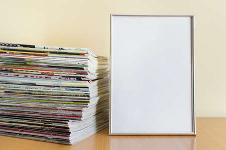 Large blank a4 silver metallic frame with blank space and huge stack of magazines on wooden surface. 免版税图像