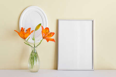 Two frames A4 and oval white frame with orange summer lily in glass vase on yellow wall background.