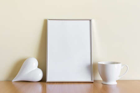 Mockup template with A4 silver frame, white porcelein heart and porcelein white cup.