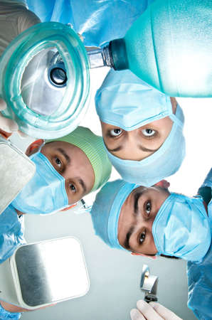 intubation: Three anesthesiologist in the operating room with an oxygen mask, defibrillator and blade for intubation.