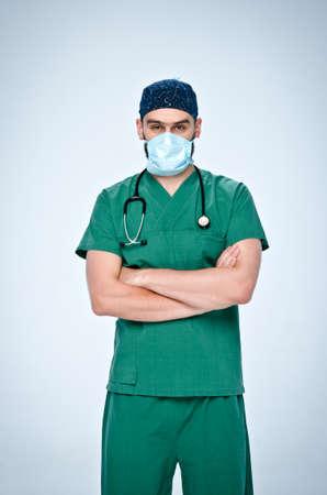 El doctor en verde friega, máscara y la tapa cruzó los brazos sobre el pecho. De su cuello cuelga un estetoscopio pediátrico médico negro. Foto de archivo