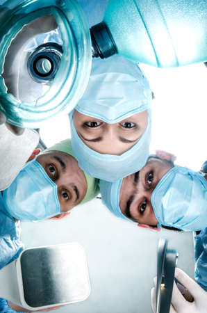intubation: Three doctors in the operating cost of the patient. Doctor wearing surgical suits, masks and gloves. In their hands they hold deffibrilyator, breathing mask and blade for intubation. Stock Photo