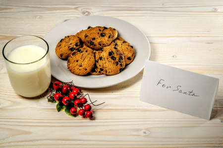Cookies and milk for Santa Claus on a wooden table. Close to treat is a card with a note.