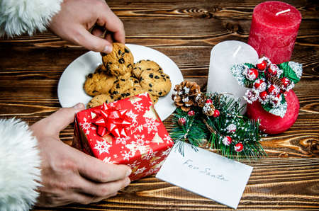 Santa Claus putting gift and takes a cookie left for him treats. Stock Photo