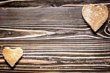 love declaration: One big and little heart from bread on a wooden surface of brown.