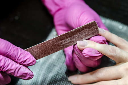 Manicurist in pink gloves file nails nail file and adjusts the shape of the nail.