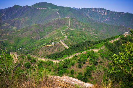 Great Wall of China on Mutianyu segment runs through the green mountains under the blue sky. Stock Photo