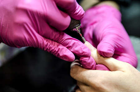 Adjusting the length of the nail with a router after applying the gel polish.