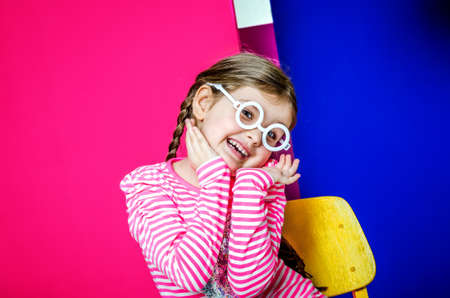 A little girl in white round glasses on a bright colored background. The girl cheerfully smiles and holds her face in her hands.