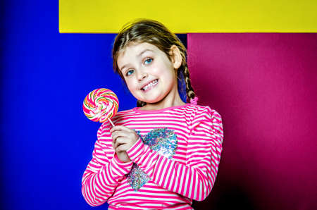 The girl is holding a large multi-colored candy and smiling.