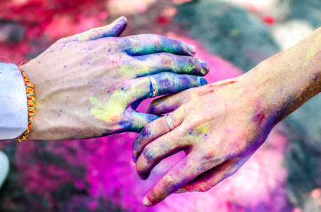 nominated: Two hands, stained with paint Holi. Nominated fingers are wearing wedding rings.
