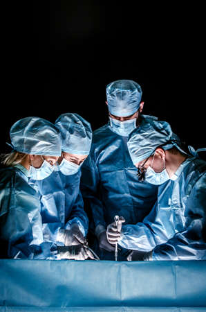 The doctor makes sternotomy during a thoracic operation. Doctors are dressed in one-off blue surgical suits, on their faces they have medical masks, and on their heads surgical caps.