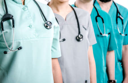 Doctors dressed in surgical suits stand in a row. On the necks of doctors hang black phonendoscopes. Stock Photo