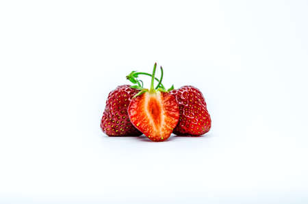 Two red whole ripe strawberry berries and a cut berry in the foreground.