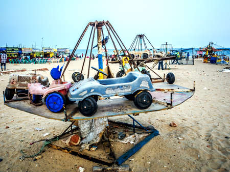 Abandoned childrens carousels in the form of cars on the beach among the garbage. Stock Photo