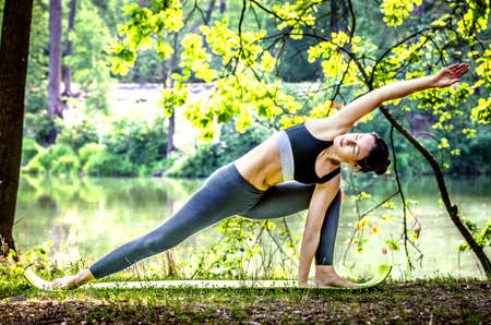 ide: Girl doing stretching exercise in nature. Stock Photo