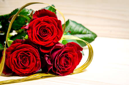 Beautiful red roses are shrouded in a golden ribbon, which has a heart shape. Stock Photo
