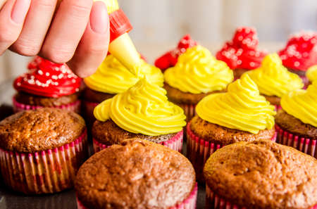 Application of yellow cream on muffins. Stock Photo