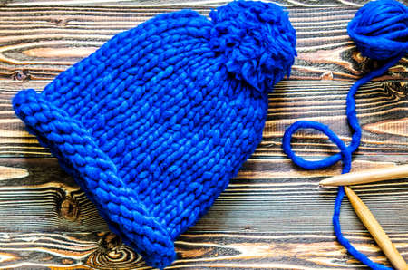 Blue knitted cap of merino wool, bamboo knitting needles and a tangle of thread.