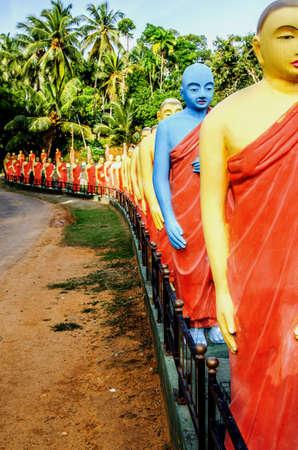 Una estatua de un monje de color azul entre las estatuas de monjes de pie en una fila en uno de los templos budistas de Sri Lanka. Foto de archivo