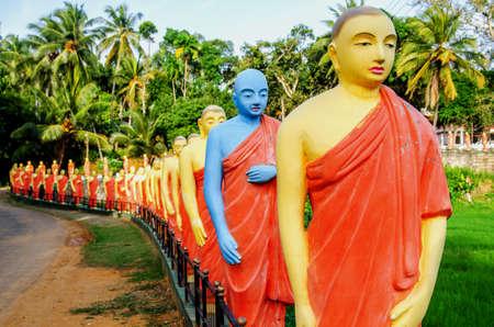 Estatuas de monjes de pie en una fila, en uno de los templos budistas de Sri Lanka. Entre las estatuas hay una estatua de un monje, pintada de azul.