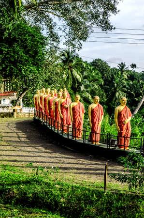 Estatuas de monjes de pie en una fila, en uno de los templos budistas de Sri Lanka.