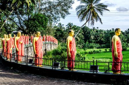 Estatuas de monjes de pie en una fila, en uno de los templos de Sri Lanka. Foto de archivo