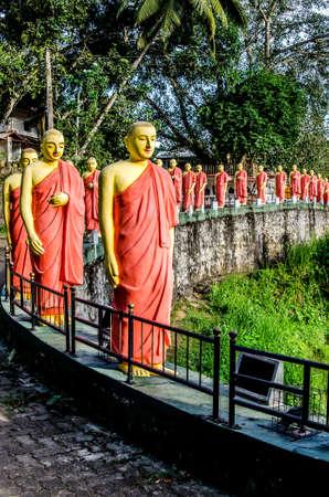 Estatuas de monjes budistas de pie en una fila en uno de los templos de Sri Lanka.