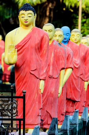 Estatuas de monjes de pie en una fila detrás del Buda en uno de los templos de Sri Lanka.