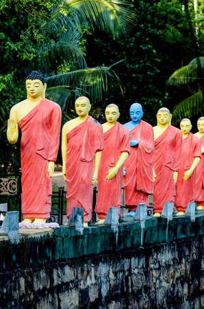 Estatuas de monjes de pie en una fila detrás del Buda en uno de los templos budistas de Sri Lanka. Foto de archivo