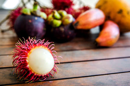 Half-peeled rambutan on the background of different fruits on the table.