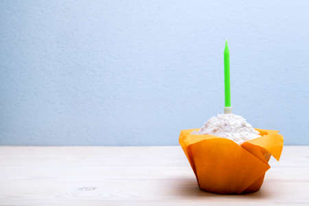 Festive birthday muffin with a bright candle.