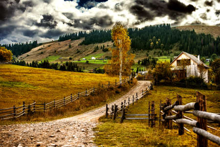 Autumn village in a mountain valley and heavy cloudy sky over the slopes. Carpathians. Ukraine. Banco de Imagens