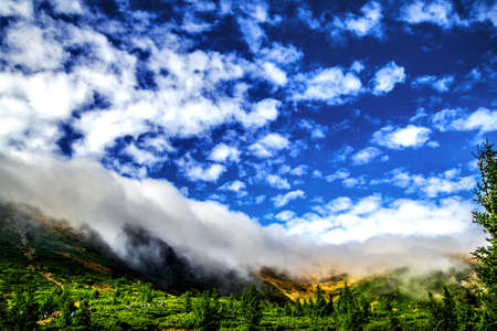A cloud, like an avalanche coming down from the mountains and covering the top. Carpathians. Ukraine. Banco de Imagens