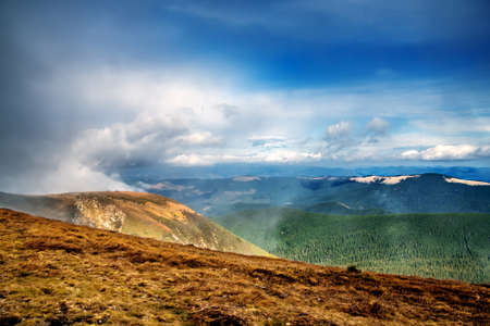 View from Mount Zaroslyak through the fog to the mountains and clouds floating above them. Carpathians. Ukraine.