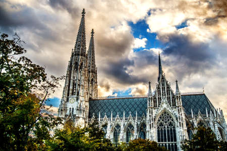 Incredibly beautiful Votivkirche Cathedral among the trees against the sunset cloudy sky. Vienna Austria