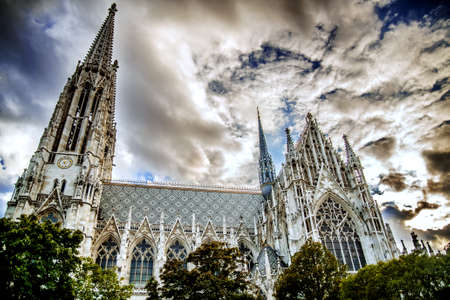 Incredibly beautiful cathedral of Votivkirche against a sunset cloudy sky. Vienna Austria