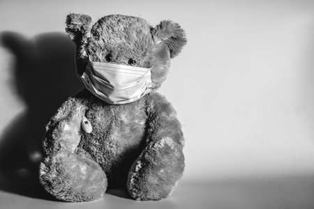 Teddy bear in a protective medical mask and with a thermometer. 写真素材