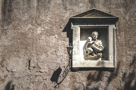 Street sculpture of the Virgin Mary with a baby on one of the walls of Rome. Italy