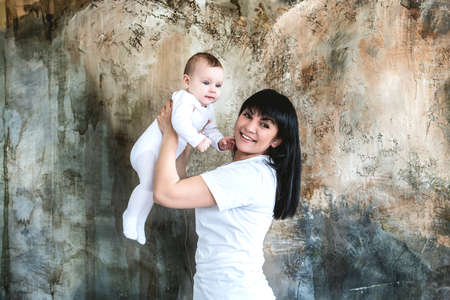 Mom plays with her newborn daughter, holding her in her arms. 写真素材